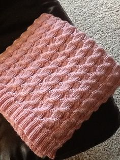 This pattern includes written and charted instructions. There is a link to a YouTube tutorial on cabling without a cable needle. The blanket is reversible.