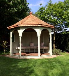 Sunbury Octagonal Gazebo with cedar shingle roof, beautifully arched openings and seating with sumptuous upholstery.