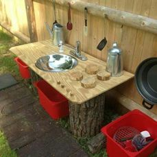 Mud Kitchen idea. Great outdoor play space created using logs, an old sink and a piece of hardboard. #Nurture@Home