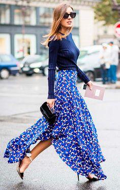 Street style look com suéter azul e saia longa estampada.