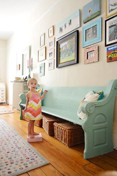 love the play of the soft pink wall, the aqua pew, and all the frames