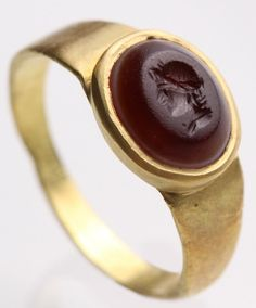 Jewelry Auction - NO RESERVE ITEM - Nov 30th 2016 - Garnet Intaglio with the Bust of a Warrior. Such flat hammered gold bands set with an oval intaglio, probably symbolic to the wearer, were fashionable in Roman times in the 1st century AD. A reddish agate is incised on its oval table with a profile bust of a warrior wearing a prominent laurel wreath (or possibly a Diadoumenos, a youthful figure with a ribbon wrapped around his head). This and more important art for sale on CuratorsEye.com