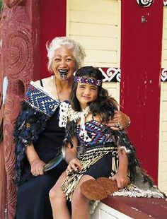 Maori grandmother and her granddaughter outside what looks like their village Wharenui (the tribe's main meeting house) - New Zealand; Love this!