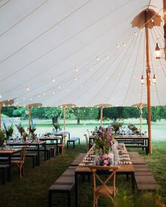 Even though the night got a bit chilly, Lilly and Carter couldn't bring themselves to close the sides of their sailcloth tent and block the magical ocean view at their Massachusetts celebration. Above, dimmed string lights hung at random heights so they swayed softly throughout the space.