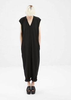Oversized, sleeveless V-neck jumpsuit with dropped shoulders and a dropped inseam in a black viscose and virgin wool blend