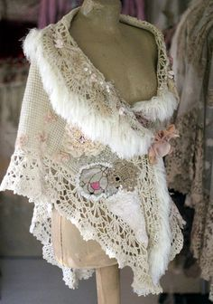 Bold shabby chic cape/shrug is reworked from vintage woven wool, crocheted lace border. Adorned with various antique laces and trims, silk roses, appliques, hand beading and bold silk chiffon blooms. Fastens at front with sculpted pale peach floral brooch.The edges are trimmed with silky ivory shade fiber which look like feathers or fur. One of a kind piece.