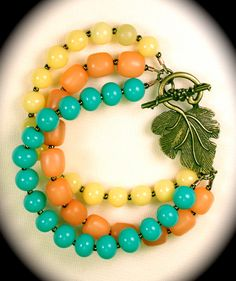 Three strand beaded bracelet with turquoise, yellow and coral beads with antiqued brass toggle.