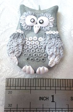 Polymer clay Owl pendant, handmade with applique technique, one of a kind. Silver with wings and feathers in gradient from dark silver to white. By Lis Shteindel.
