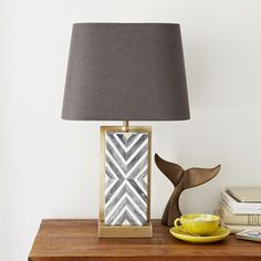 Natural bone tiles are hand-inlaid in a herringbone pattern on both sides of a plated antique brass metal base to create this Chevron Deco Table Lamp. Its compact silhouette makes it just the right fit for a desk or living room side table.