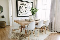 Dining space with a cowhide area rug, modern white chairs, and modern art