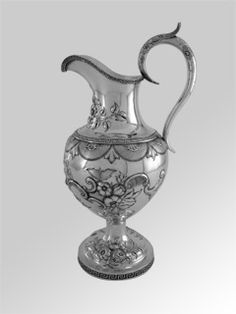 "An American Coin Silver Water Pitcher, maker's mark of Peter L. Krider for J. E. Caldwell & Co., Philadelphia, circa 1850. Of baluster form on a domed circular foot, applied with die-rolled Greek key borders and chased with blossoms, leaves, and shells enclosing a vacant reserve opposite the handle, engraved in a feathered script typical of the period ""J.P. / to / S.A.L."", the leaf-capped upswept handle repeating the chasing; height is 15 1/2 inches, weight is 28.18 Troy ounces."