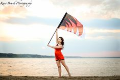 2014 High School Senior girl for posing picture ideas. Senior girl posing in front of water at sunset color guard or flag for band inspiration idea. High school senior session pose inspiration for senior pictures for color guard or flags.