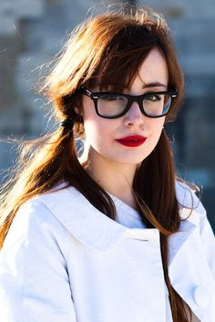 Black glasses and red lipstick.