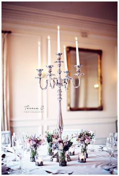 Our silver candelabra can be used on their own for an elegant table centrepiece or you can have pretty vases of flowers dotted around the base. Captured by Teresa C Photography