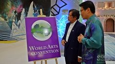 Abang Johari looking at the World Arts  Convention poster while Goh explains the event to him.
