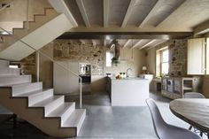 Beautifully restored stone house in Spain with classic mid-century furniture, large kitchen island, sleeping loft with deck & skylights by Dom Arquitectura. Scandinavian Interior Design, French Interior, Architecture Renovation, Traditional Style Homes, Large Kitchen Island, Stone Facade, New Kitchen Designs, Stone Houses, Concrete Floors