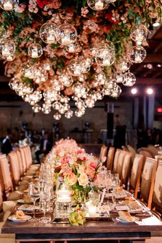Hanging floral and tea light installation above wedding reception tables