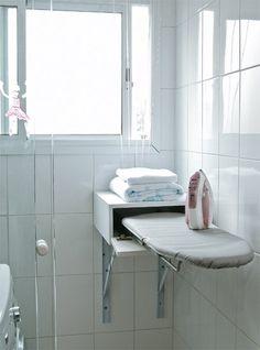 A tábua de passar roupa surge de dentro de uma caixa de MDF apoiada em mãos francesas dobráveis. O utensílio dobra ao meio e se recolhe dentro da caixa, deixando a circulação livre na lavanderia de 2 m² (2 m²!!! é uma caixa de fósforos!)