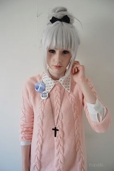 Cute, sweet gyaru: Black bow. Light gray wig. White shirt with black dots. Light pink, cable knit cardigan. Necklace. Pins.