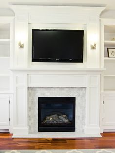 Love the built-ins, fireplace tile, sconces, floor, and rug. Just perfection.