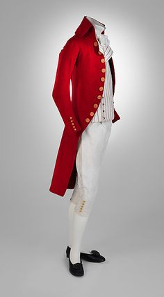 Wool coat 1787-92. Here is a dashing coat that anticipates the Macaroni exaggeration that will characterize menswear in the 1790s. In this early example, the proportions are already attenuating; there is a very high turn to the collar, though not yet to the point of caricature