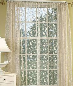 Berries, birds, leaves and vines  are silhouetted against a simple sheer background. (Country Curtains Bird Song Lace Rod Pocket Curtain Panel)