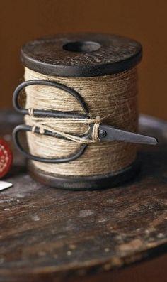 Antique scissors and spool of thread.