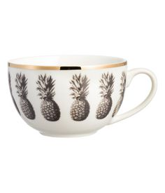 White/gold-colored. Porcelain mug with a printed pineapple pattern. Gold-colored trim at top. Height 3 in., diameter at top 4 1/2 in.