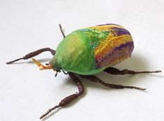 This green flower beetle is approx 4 1/2 inch tall and 2 inch wide made with cotton fabric. They are hand painted and hand embroidered with details. It is free stand sculpture but also have a metal hoop on the back for hanging.