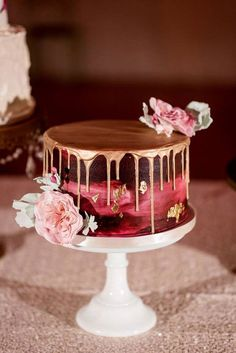 Burgundy painted wedding cake with gold drip and gold leaf, topped with pink flowers.