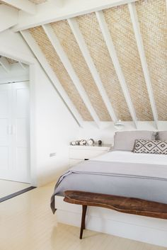 Upstairs, an airy bedroom under the woven bamboo ceiling. The floor is painted in Benjamin Moore Pale Moon, a subtle buttery yellow.