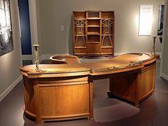 """The curved """"Secession desk"""" by Henry van de Velde combines elegance and functionality in perfect shape. In the background, a glass-fronted bookcase, which the GNM after Van de Velde show acquired in 1993. (""""Der geschwungene """"Sezessions-Schreibtisch"""" von Henry van de Velde vereint Eleganz und Funktionalität in schönster Form. Im Hintergrund ein verglaster Bücherschrank, den das GNM nach der Van de Velde-Schau 1993 erwarb"""").."""
