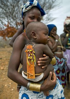 Mucubal baby and his wood talisman - Angola by Eric Lafforgue, via Flickr