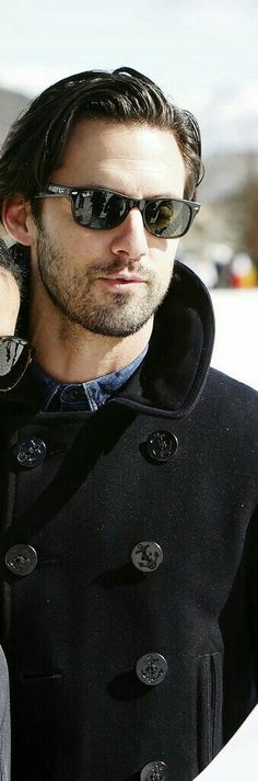 Thick stubble, denim shirt, contrasting winter peacoat with shades