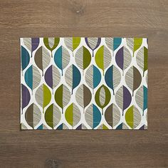 Graphic leaves composed of casual lines and solid cool tones decorate this placemat with rich color and dynamic pattern. Screenprinted on cotton, the placemat pairs with a matching napkin for a lively fall table.