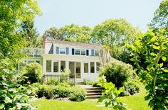 Betsey Johnson's Traditional Hamptons Home // White house with blue shutters and large glass windows