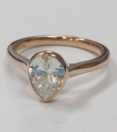 ring features a bezel set center diamond
