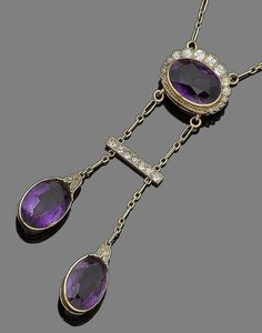 An amethyst and diamond pendant necklace.  The central oval-cut amethyst within a graduated surround of old brilliant-cut diamonds, suspending a bar set with similarly-cut diamonds, terminating in two oval-cut amethyst drops of unequal length, each capped by rose-cut diamonds, to a figaro-link chain, lengths: pendant 7.8cm, chain 38.5cm