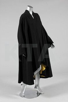 A Paquin couture black moss crepe swing-coat, circa 1950, large woven label, with graduated hem from front to back, lined in yellow crepe, Kerry Taylor Auctions