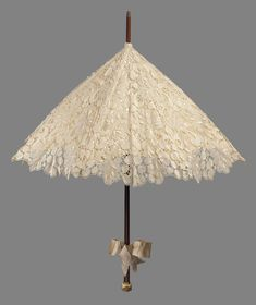 Cream colored silk bobbin lace parasol in heavy symetrical design of ornamental leaves, lined with cream colored satin bow tied on plain brown wooden handle, knob of carved ivory with monkey picking fruit at end of handle.