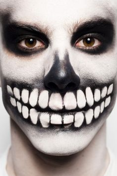 Skull face paint. Start with a well blended white face. Sponge on black around the mouth and eyes and nose. Blend out softly. Add teeth with a brush.