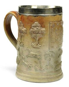 AN ENGLISH SALT-GLAZED BROWN STONEWARE SILVER-MOUNTED MUG  CIRCA 1750, PERHAPS BRISTOL.  Sprigged with a figure drinking punch and smoking in an interior, above a stag hunt