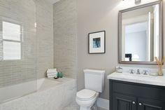 bathrooms - gray walls black single bathroom vanity marble countertop marble herringbone tiles floor seamless glass shower gray glass subway tiles shower surround