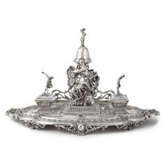 A French silver presentation inkstand, probably Tetard, Paris, circa 1875 shaped oval base on openwork feet, centered by a muse with slate with presentation inscription, flanked by two square compartments for sand and ink (liner missing to latter) with finials formed as Mercury and Victory, backed by an openwork panel with espagnolettes supporting a bell topped by a half-draped female with a torch