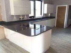 Ultra modern gloss white handless kitchen with quartz grey worktops.