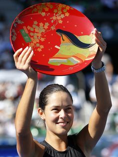 Ana Ivanovic of Serbia holds up the winner's plate during an award ceremony after beating Caroline Wozniacki of Denmark in their final match at the Toray Pan Pacific Open tennis tournament in Tokyo Sunday, Sept. 21, 2014. (AP)