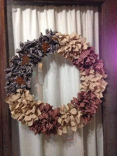 A beautiful hand crafted patriotic wreath with a rustic look. 24 made with homespun fabric tied on and 3 metal stars.    This patriotic rag wreath
