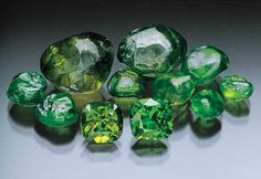 A bevy of beauties from the Ural Mountains in Russia. Demantoid such as this has not been seen since the time of the Czars. The cut stones are over 4 cts. each. (Photo: Jeff Scovil/Pala International)