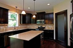 """kitchen design ideas. Consider 42"""" cabinets, glass in corner cabinet. Cabinets and molding up to ceiling. Cream color instead of dark."""