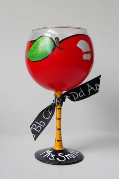 This teacher themed red wine glass has been hand painted like a red apple for teacher. Stem depicts a ruler and base of glass can be personalized
